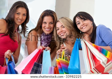 group of friends smiling with shopping bags in a mall - stock photo