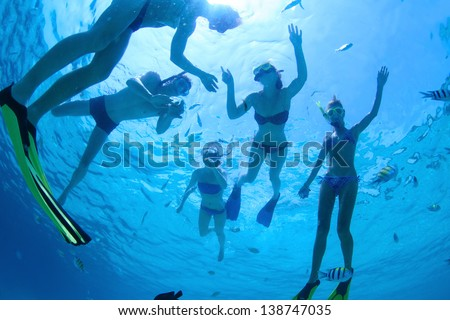 Group of friends snorkeling in a tropical sea - stock photo