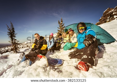 Group of friends snowboarders and skiers relaxing in camp near tent  on the slope of ski resort Sheregesh. Siberia, Russia - stock photo