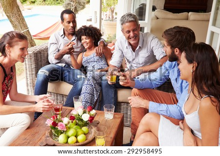 Group of friends socialising in a conservatory - stock photo