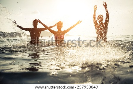 group of friends splashing water in the sea at patong beach, phuket. concept about people and fun - stock photo