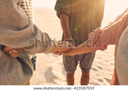 Group of friends stack their hands together. Young men and women standing together at the beach stacking their hands, concept of unity and teamwork. - stock photo