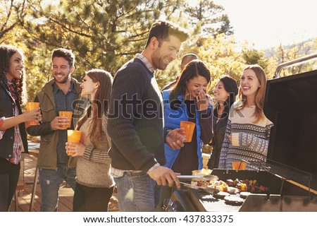 Group of friends stand at a barbecue, one cooking at grill - stock photo