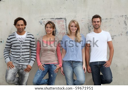 Group of friends standing against wall - stock photo