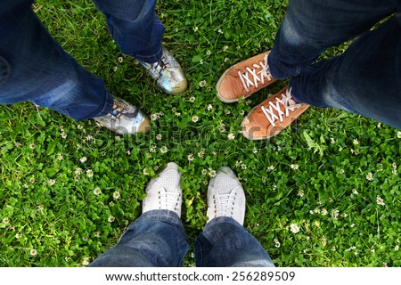 Group of friends standing in a circle on a spring meadow but only their feet in sneakers is visible - stock photo