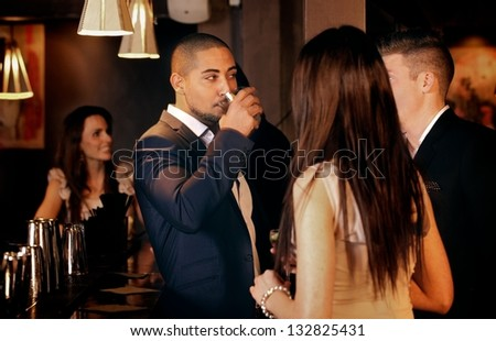 Group of friends standing while having conversation at a bar - stock photo