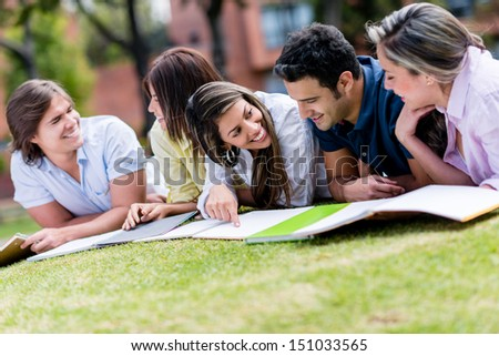 Group of friends studying outdoors at the park  - stock photo