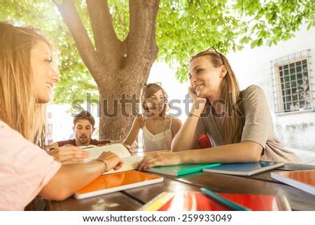 Group of friends studying under a tree on a wooden table - stock photo