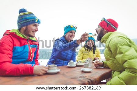 group of friends take a break in a mountain chalet. Eating hot chocolate and cakes - stock photo