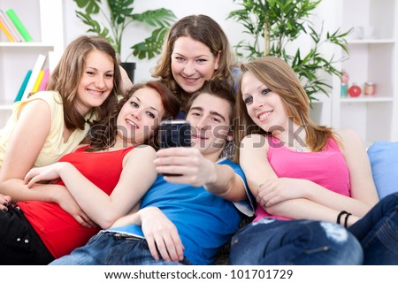 group of friends taking a picture of themselves on cell phone - stock photo