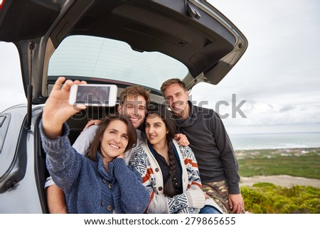 Group of friends taking a roadtrip along the coast posing for selfie at the back of their car - stock photo