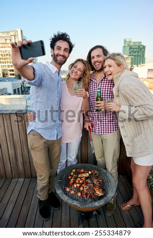 Group of friends taking a selfie at their outdoor rooftop barbeque - stock photo