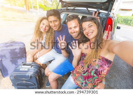 Group of friends taking a selfie in the back of the car before leaving for vacations. They are a mixed race group of four persons, two caucasian and two hispanic. - stock photo