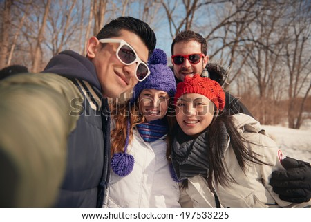 Group of friends taking a selfie in the snow in winter