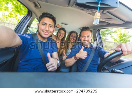 Group of friends taking a selfie into the car before leaving for vacations. They are a mixed race group of four persons, two caucasian and two hispanic. - stock photo