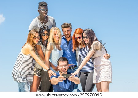 Group of friends taking a selfie - Multiethnic group of students taking a self portrait with cell phone as memory of fantastic holiday  - stock photo