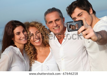 Group of friends taking picture of themselves at the beach - stock photo