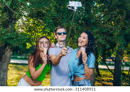 Group of friends taking picture of themselves with monopod use smart phone take photograph selfie stick in park - stock photo