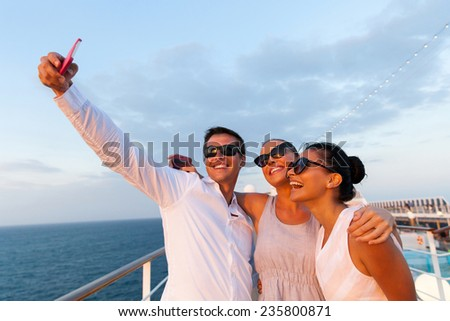 group of friends taking self portrait using smart phone on cruise - stock photo
