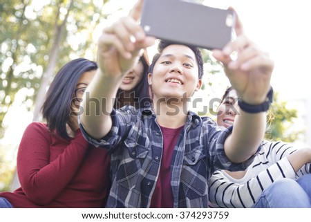 Group of Friends taking Self Portraits with Mobile Phone - stock photo