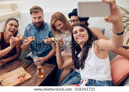 Group of friends taking selfie on a smart phone. Young people eating pizza on rooftop party taking selfie. - stock photo