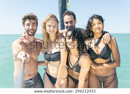 group of friends taking selfie on the boat while cruising. concept about mixed race groups of friends. - stock photo