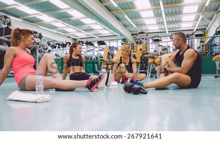 Group of friends talking sitting on the floor of a fitness center after hard training day - stock photo
