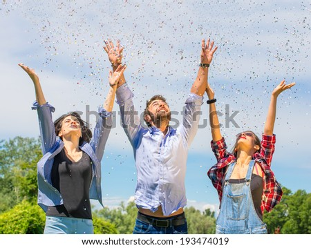 Group of friends throwing confetti in the air - happiness concept - stock photo
