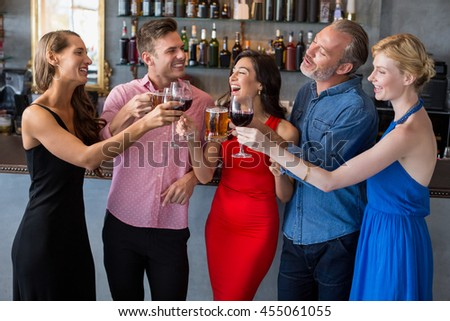 Group of friends toasting glasses of beer and wine in restaurant - stock photo