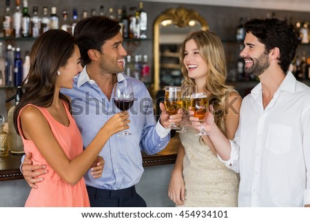 Group of friends toasting red wine and champagne in bar