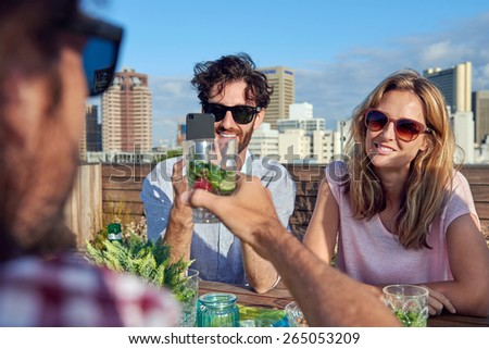 Group of friends toasting to a celebration with drinks while hanging out at a restaurant on a rooftop terrace - stock photo