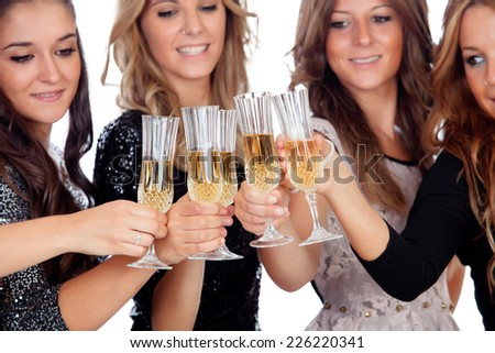 Group of friends toasting with champagne in a celebration during christmas - stock photo