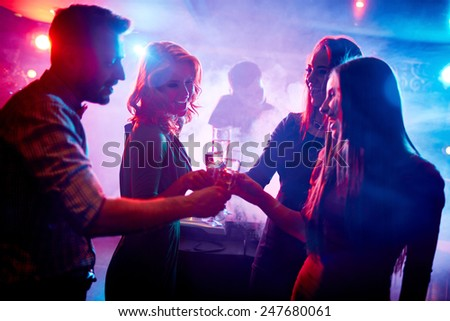 Group of friends toasting with champagne in night club - stock photo