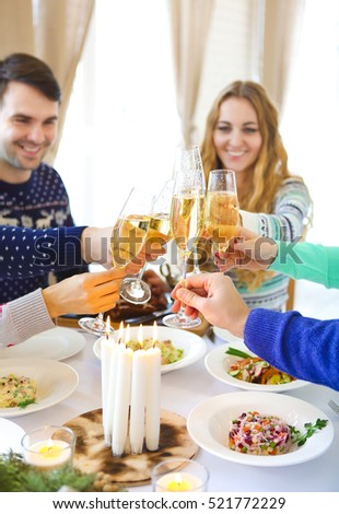 Group of friends toasting with champagne while having Christmas dinner