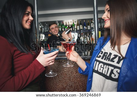 Group of friends toasting with cocktails in the bar