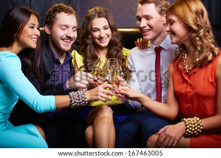 Group of friends toasting with flutes of champagne in the bar - stock photo