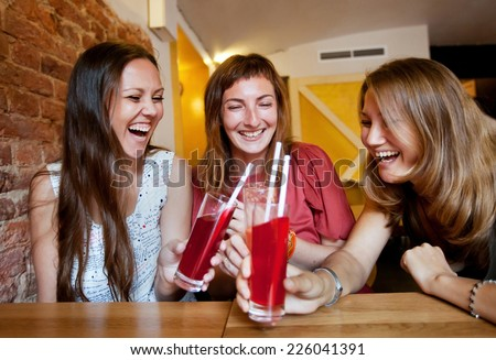 group of friends together in cafe, young girls laughing and celebrating - stock photo