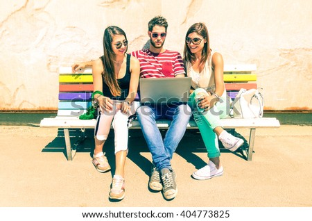Group of friends using laptop on travel holiday in sunny summer day - Teenagers on vacation with computer sitting together on bench outdoors - Concept of wireless internet browsing and teenage culture - stock photo