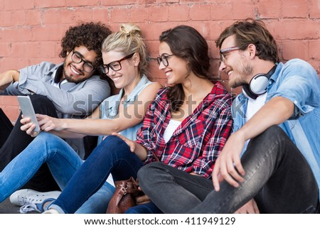 Group of friends using mobile phone - stock photo