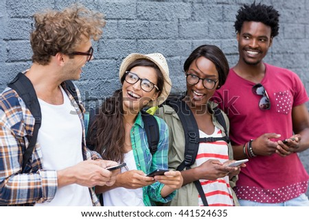 Group of friends using mobile phone and having fun - stock photo
