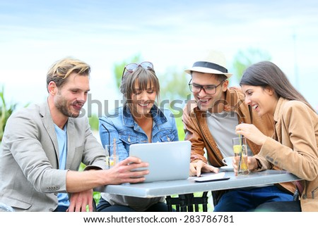 Group of friends using tablet while having a drink - stock photo