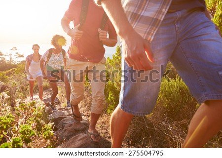 Group Of Friends Walking Along Coastal Path Together - stock photo