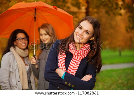 group of friends walking in autumn park - stock photo