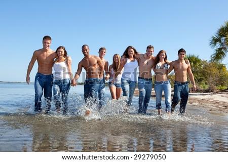 Group of friends walking on a beach, all in jeans