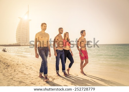 Group of friends walking on the beach at sunset - Four people of different ethnic having fun  - stock photo