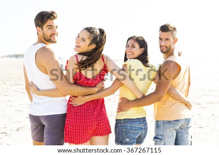 Group of friends walking together at the beach and looking back - stock photo