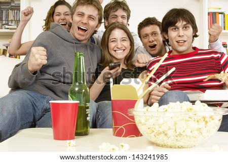 Group of friends watching television and cheering in living room - stock photo