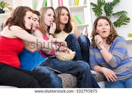 Group of friends watching TV, something very interested happened on the screen.