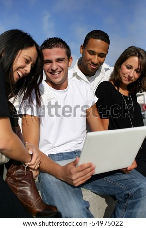 Group of friends with a laptop computer - stock photo
