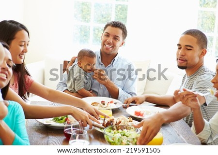 Group Of Friends With Babies Enjoying Meal At Home Together - stock photo